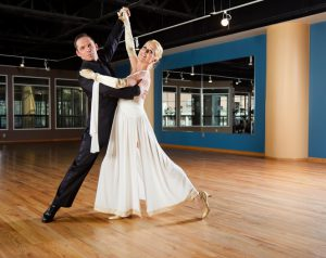 A couple ballroom dancing in an empty dance studio.